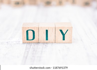 The Abbreviation DIY Formed By Wooden Blocks On A White Table