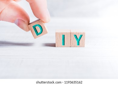 The Abbreviation DIY Formed By Wooden Blocks And Arranged By Male Fingers On A White Table