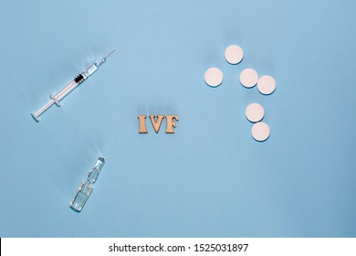 The abbreviation IVF is laid out in wooden letters on a blue background. In vitro injection pen, tablet and ampoule. A syringe with a thin huge. IVF concept. Medication with hormones. Infertility