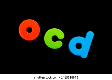 The abbreviation OCD (Obsessive Compulsive Disorder) spelt with brightly coloured letters over a black background.