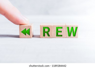 The Abbreviation REW Formed By Wooden Blocks And Arranged By A Male Finger On A White Table
