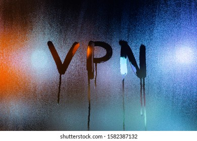 an abbreviation VPN - virtual private network drawed by finger on night wet glass with smudges of water