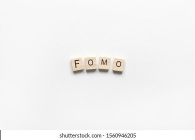 Abbreviation word FOMO from wooden blocks on white background. FOMO means Fear Of Missing Out, non-stop internet surfing. Concept social communication problem between people, digital detox. Flat lay.