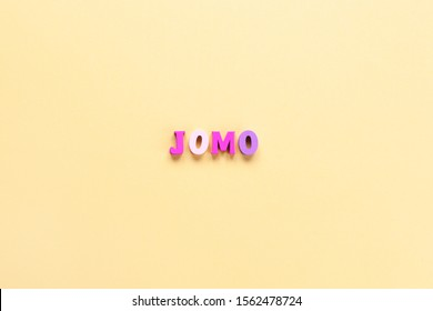 Abbreviation word JOMO in multicolored wooden letters on pastel yellow background. JOMO - Joy Of Missing Out. Opposition, choice, social problem, digital detox. Flat lay, copy space, minimalism style.