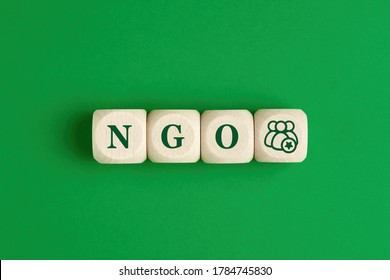 The abbreviation word NGO nongovernmental organization written on wooden cubes with group of people icon on green background
