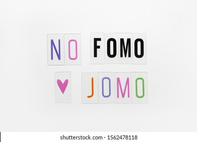 Abbreviation words FOMO, JOMO on transparent plastic on white background. FOMO means Fear Of Missing Out. JOMO - Joy Of Missing Out. Opposition, choice, social problem, digital detox. Flat lay.
