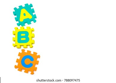 ABC alphabet on colorful pieces of puzzle on white background, early education concept