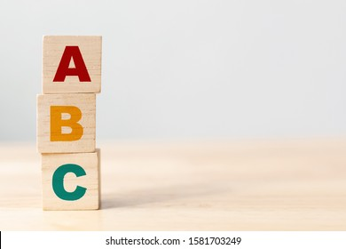 ABC letters alphabet on wooden cube blocks in pillar form on wood table