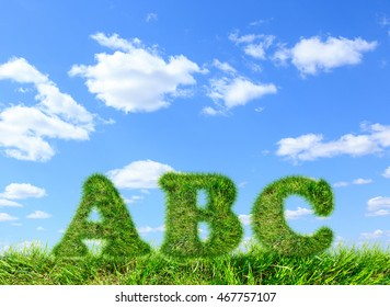 ABC made of green grass on blue sky background