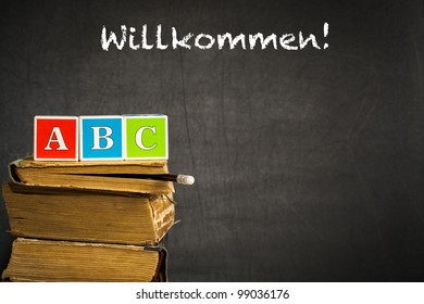 "ABC on old books against blackboard with text ""Welcome!"" in the German language. School concept"