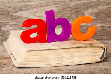 ABC spelling and old book on wooden background