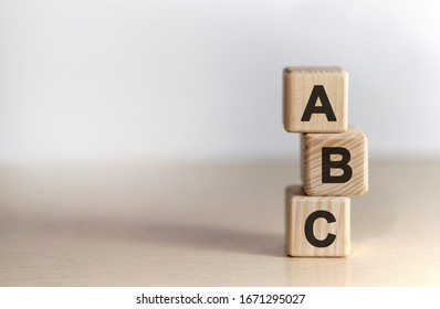 ABC - text on wooden cubes, on wooden background