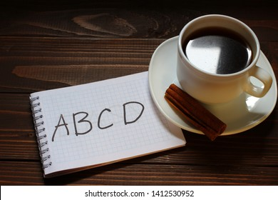 ABCD inscription and word in a notebook near a cup of coffee