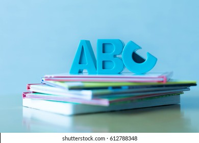 ABCs symbols placed on a stack of educational children's books.