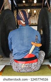 Abdi dalem of Keraton Yogyakarta's costume with blangkon, keris and traditional fabrics