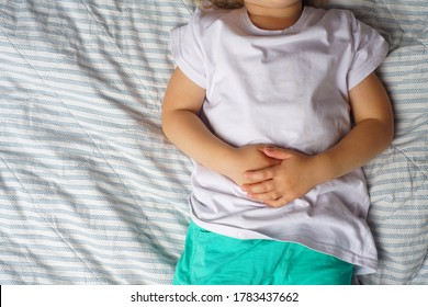 abdominal pain in a preschool child. poisoning in children. the boy holds his hands to the abdominal cavity