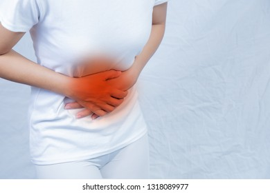 Abdominal pain of a young woman. Taken from the front view on a white background. Abdominal pain Menstrual pain of women