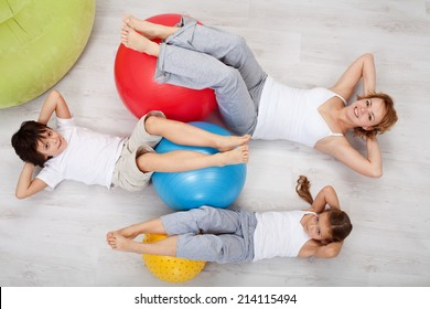 Abdominal workout - woman and kids doing gymnastic exercises, top view