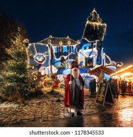 Abensberg, Germany - December 8, 2017: Saint Nicholaus stands in front of Hundertwasser Art Museum Kunsthaus with Christmas illuminations and loads of shining decoration merchandise.