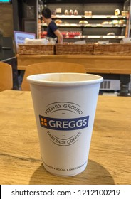 ABERDARE, WALES - OCTOBER 2018: Paper cup of freshly ground Fairtrade coffee on a wooden table inside the branch of Greggs in Aberdare town centre.