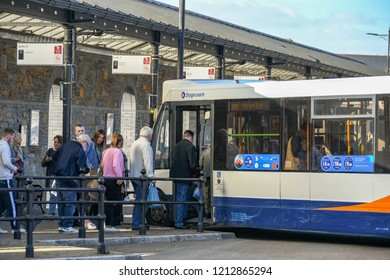 ABERDARE, WALES - OCTOBER 2018: People queuing to get on a bus in the bus station in Aberdare town centre.