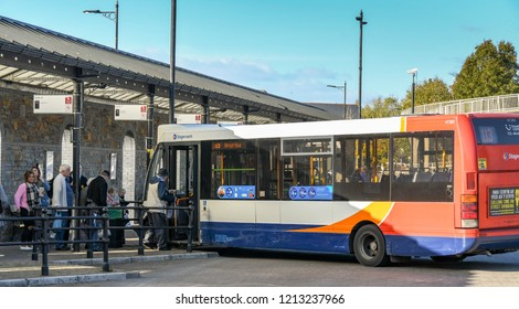 ABERDARE, WALES - OCTOBER 2018: People getting on a bus in the bus station in Aberdare town centre.