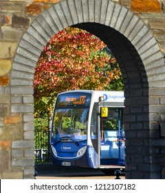 ABERDARE, WALES - OCTOBER 2018: Public service bus operated by Stagecoach Group plc viewed through one of the arched entrances to the bus station in Aberdare town centre.