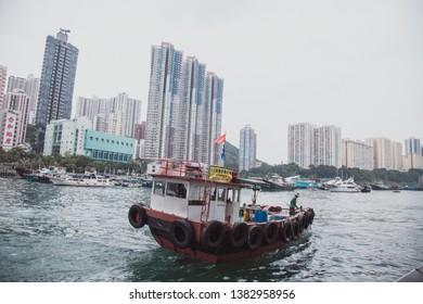 Aberdeen Bay, Hong Kong island - September 2018 : Floating House and local boat around Aberdeen Marina club in Po Chong Wan, Sham Wan estuary with Hong Kong Buildings background.