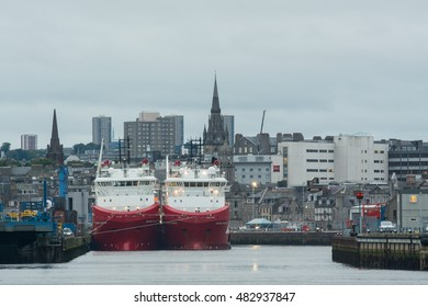 ABERDEEN, SCOTLAND, UK - 13 SEPTEMBER 2016: two large cargo ships in Aberdeen harbor dwarfing many of the old granite housing behind