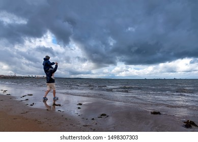 Aberdeen, United Kingdom - August 17, 2014: Father and son on the beach look at the stormy sky. Aberdeen Beach as been recognised for its popular recreational and sports area and attracts many visitor