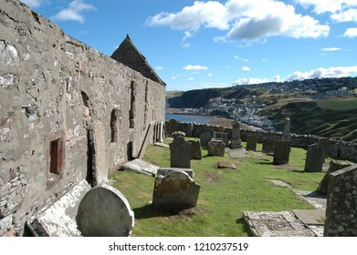 Aberdeenshire, Scotland: August 14th 2018 - Ancient ruined church of St John on clifftop above Gardenstown, Aberdeenshire, Scotland with the bay and village visible below.