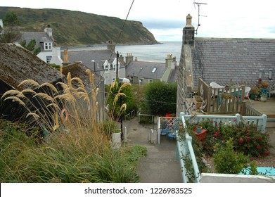 Aberdeenshire, Scotland - August 28th 2018: A quaint pathway leads through traditional fishing cottages in Gardenstown, Aberdeenshire.
