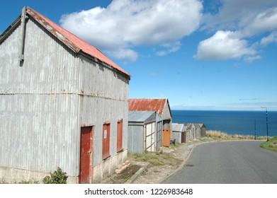 Aberdeenshire, Scotland - August 28th 2018: A collection of old sheds next to a road and the North Sea, in Gardenstown, Scotland.