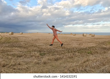 ABERDEENSHIRE, SCOTLAND - MAY 2019 : A man jumping with joy outisde the Dunnottar Castle. Stonehaven, Aberdeenshire, Scotland, United Kingdom.