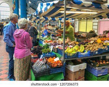 ABERGAVENNY, MONMOUTHSHIRE, WALES - OCTOBER 2018: Shoppers at a fruit and vegetables staff in the indoor market hall in Abergavenny town centre.