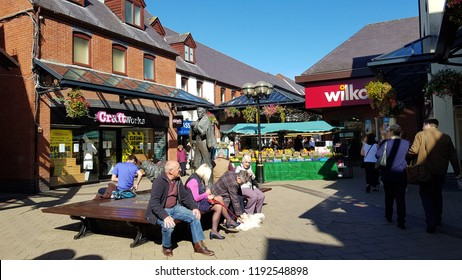 Abergavenny, UK - 09 25 2018: Street Scene with people sitting on a bench by market stall.