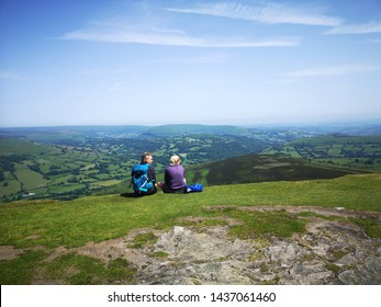 Abergavenny, UK: June 28, 2019: Hikers sit on the grass enjoying the view - Sugar Loaf Mountain is situated 2 miles north-west of Abergavenny in Monmouthshire, Wales.