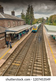 ABERGAVENNY, WALES - OCTOBER 2018: Cross country train stopped on Platform 1 in Abergavenny railway station. Passengers are walking along the platform to leave the station.
