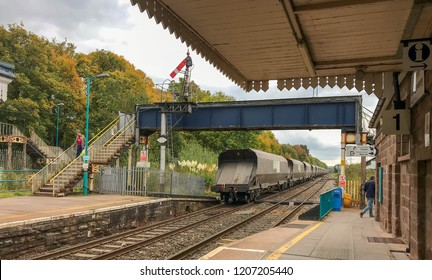 """ABERGAVENNY, WALES - OCTOBER 2018: The last wagon of a Freightliner Heavy Haul goods train passes under the footbridge at Abergavenny railway station. The signal is still in the """"down"""" position."""
