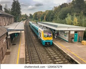 ABERGAVENNY, WALES - OCTOBER 2018: Passengers waiting on the platform as a train arrives on platform 2 at Abergavenny railway station.