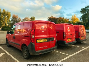 ABERGAVENNY, WALES - OCTOBER 2018: Row of Royal Mail Post Office delivery vans parked near the town's postal sorting office in evening sunlight.