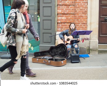 Abergavenny, Wales, UK: April 04, 2017: Busker in Abergavenny Town centre, street singer and guitar player young lady, who was singing in a public place