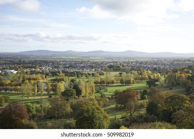 Abergele village in wales, overlooking the town with mountains on the horizon, showing trees, fields and traffic from a high distant vantage point. Autumn  orange and golden leaves green, golf course.