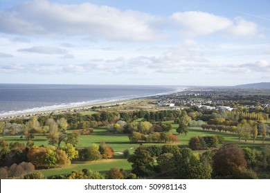 Abergele in Wales UK, overlooking the ocean coastline featuring the towns of Aberegle Pensarn, Rhyl and Kinmel bay in the distance, the foreground a gold course in Autumn with blue sky and clouds.