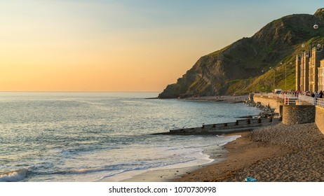 Aberystwyth, Ceredigion, Wales, UK - May 25, 2017: Evening view over the North Beach and the Marine terrace, with people on the beach and the sidewalk
