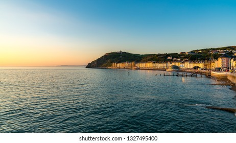 Aberystwyth, Ceredigion, Wales, UK - May 25, 2017: Evening view over the North Beach and the Marine terrace, with people on the beach and the Cliff Railway in the background