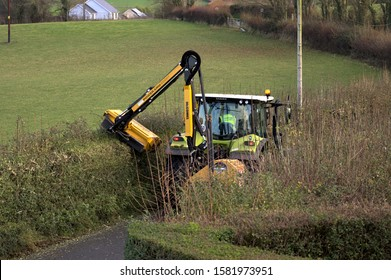 Aberystwyth Ceredigion Wales/UK December 04 2019: Yellow Tractor hedge cutting on a rural country lane