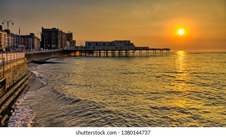 Aberystwyth Seafront on the coast to the Irish Sea with promenade and pier at sunset.