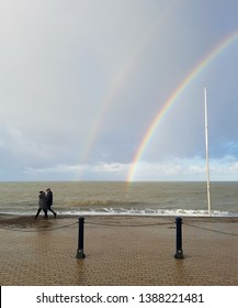 ABERYSTWYTH, WALES, UK - NOVEMBER 11 2018: Man and woman walking through rain along Aberystwyth seafront with a double rainbow appearing over the sea behind them.