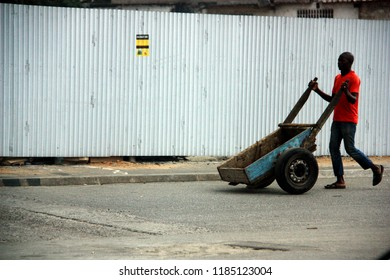 Abidjan, Cote d'Ivoire - October 1st, 2012: African man pushing his hand cart towards the market in Abidjan